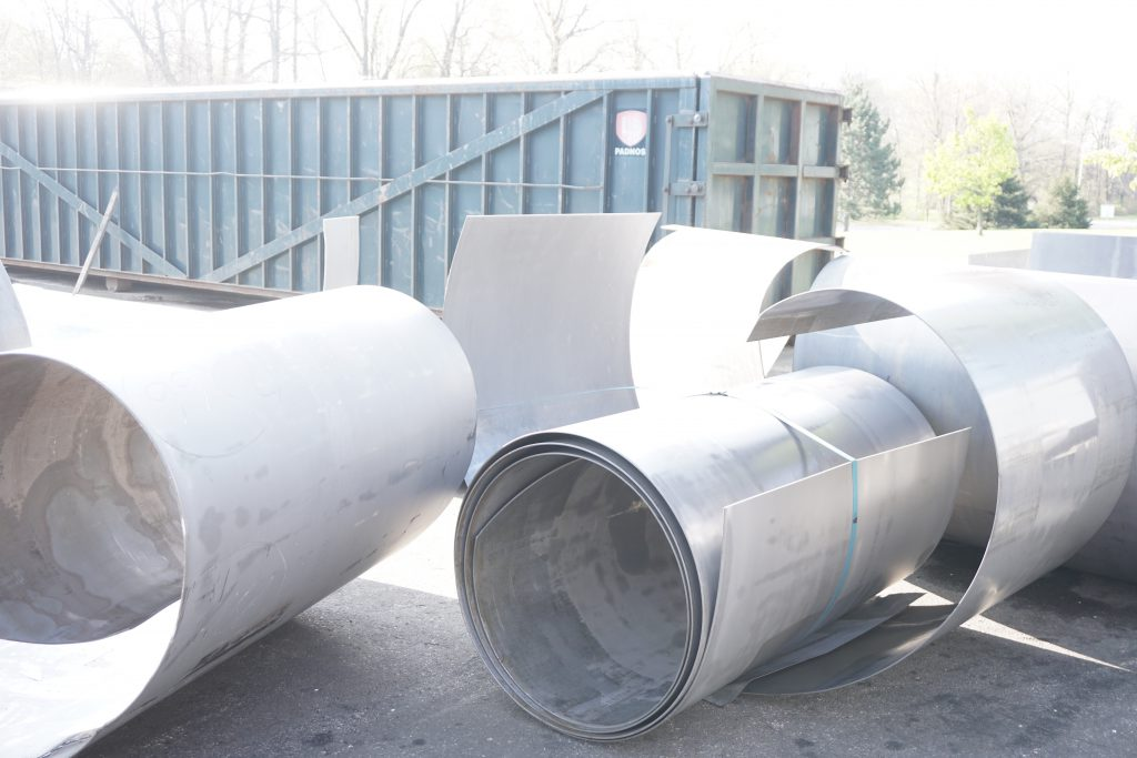 rolls of recycled steel in a scrap metal yard